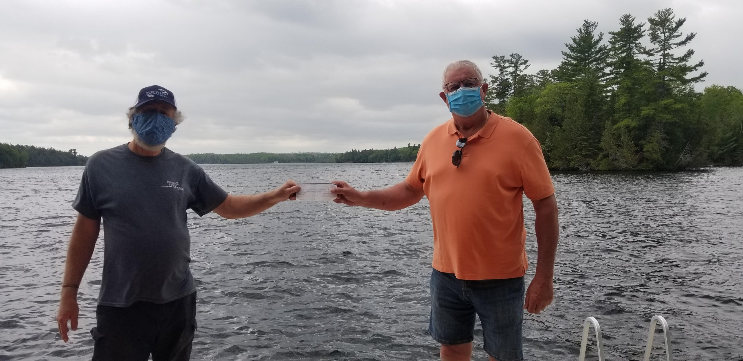Two men standing on a dock holding a cheque