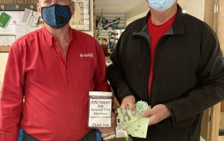 Two men holding jar of donations made by customers